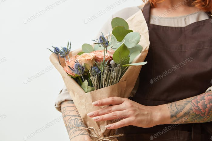Fresh flowers living coral roses and eryngium as a congratulate bouquet in girl's hand with