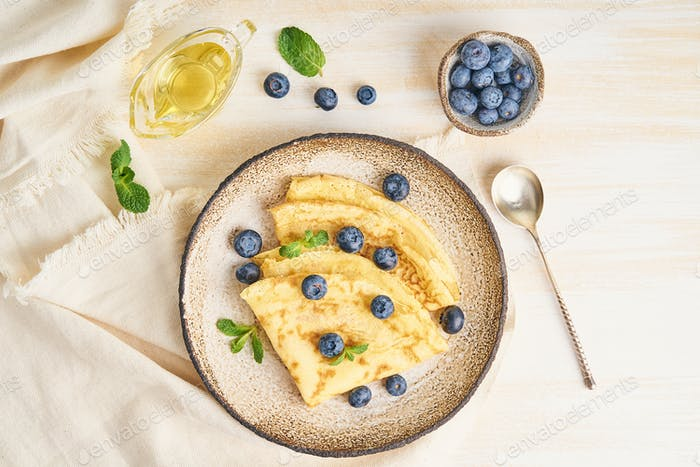 Two pancakes with blueberries and mint on plate, top view