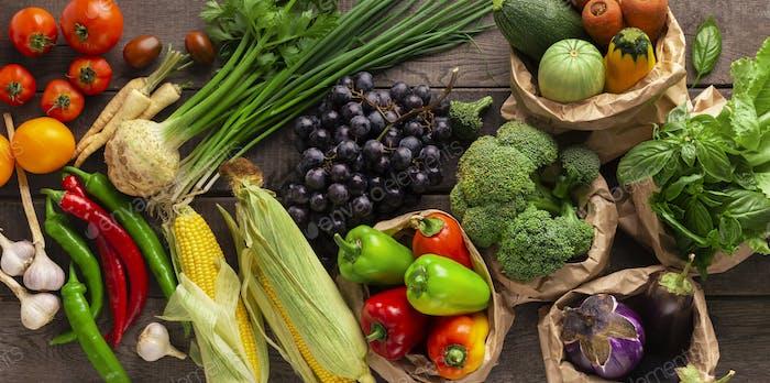 Flache Verlegung von Bio-Obst und Gemüse auf hölzernem Hintergrund