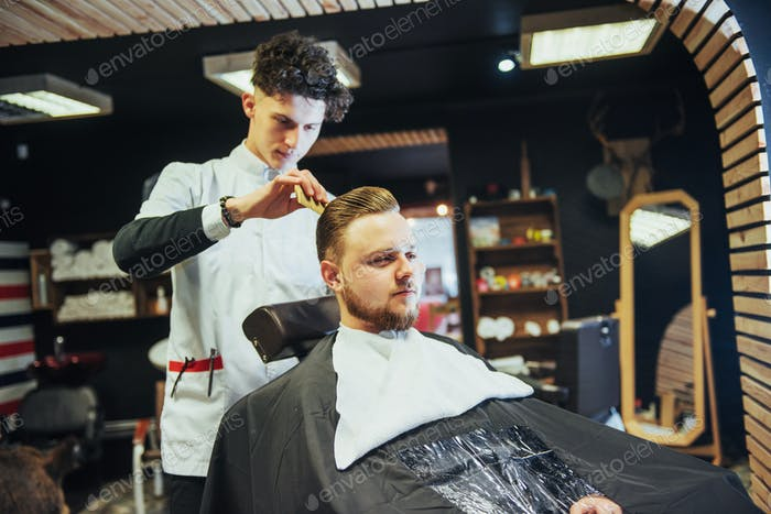 The Barber man in the process of cutting the beard of client electric clippers