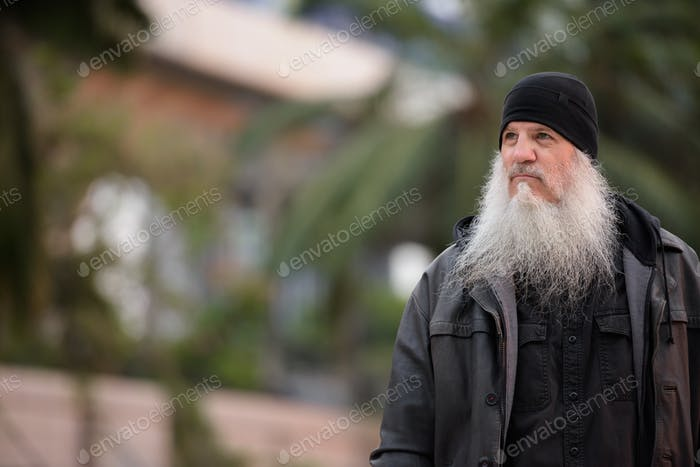 Portrait of mature handsome bearded hipster man thinking
