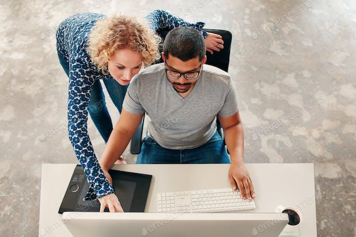 Zwei junge Designer arbeiten an einem PC