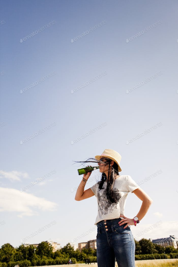 Young woman drinking beer at beach against sky