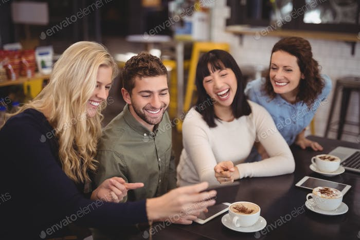 Cheerful friends using digital tablet while sitting at coffee shop