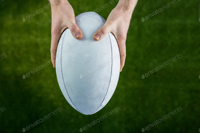Upward view of a rugby player catching a rugby ball