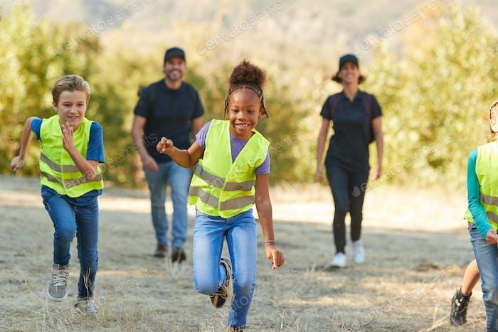 Erwachsener Teamleiter mit Kindern im Outdoor Activity Camp Freiwilligenarbeit, um mit der Umwelt zu Hilfe