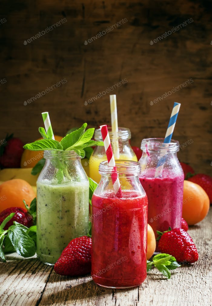 Multi-colored bottles with fresh fruit smoothies with striped straws, berries, fruit and mint