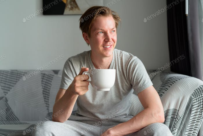 Happy young handsome man thinking while drinking coffee in the living room at home