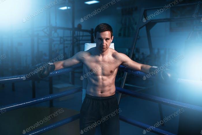 Boxer in schwarzen Handschuhen in der Ecke des Rings