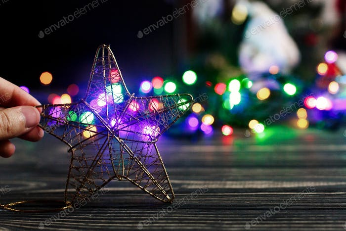 hand holding golden christmas star toy on background of colorful garland lights