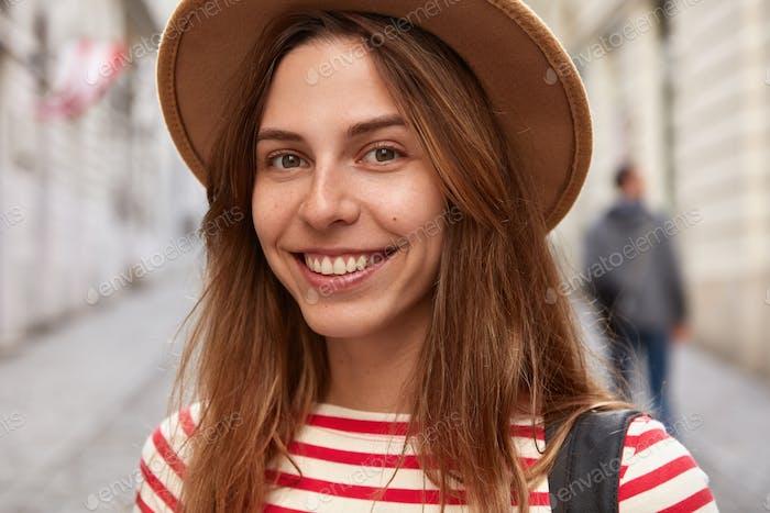 Close up shot of cheerful female adventurer wears headgear, striped jumper, has glad expression, str