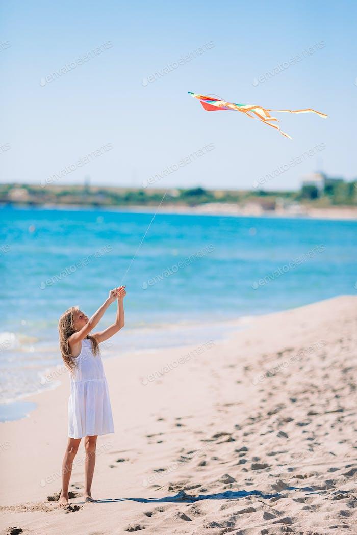 Little girl flying a kite on beach at sunset