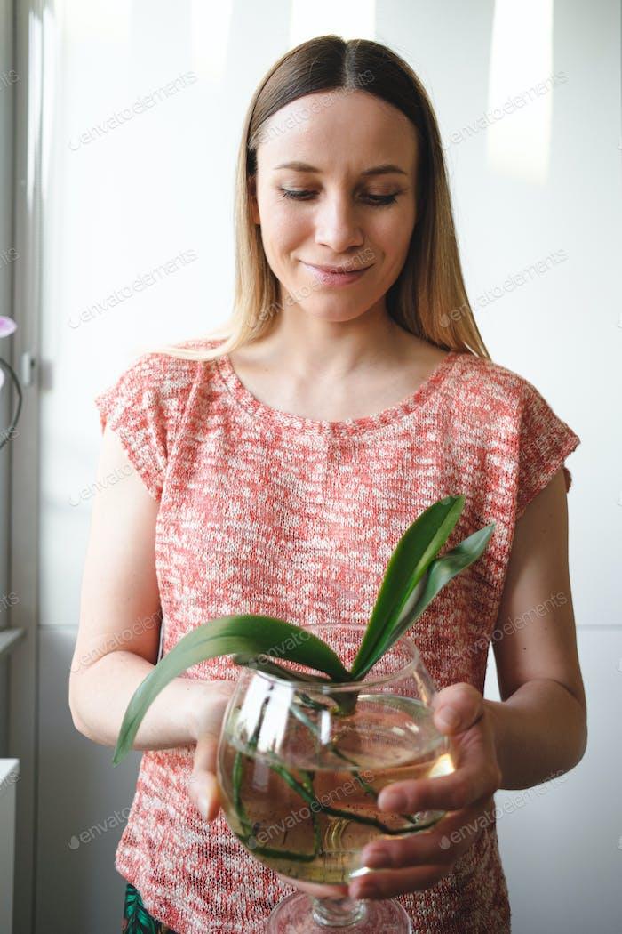 Hübsche Frau hält in den Händen eine Dose Wasser mit einer Orchideenpflanze