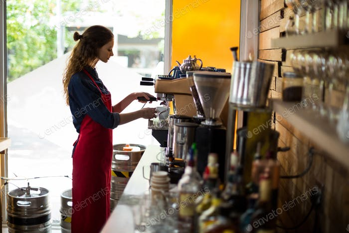 Waitress making cup of coffee at counter