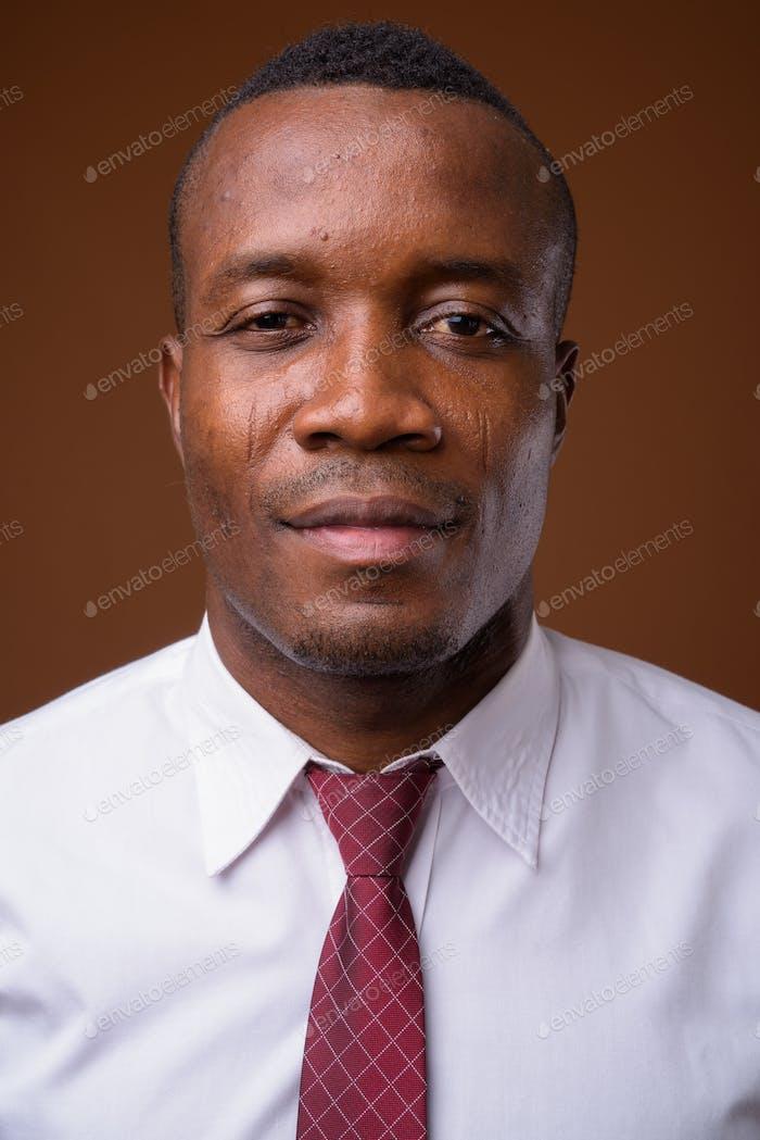 Studio Schuss von jungen afrikanischen Geschäftsmann gegen braun backgroun