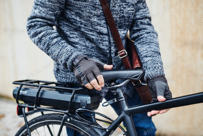 A midsection of a cyclist with electrobike standing outdoors in town.