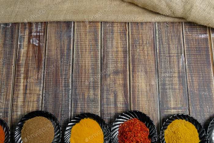 Spices in black ceramic plates on wooden background