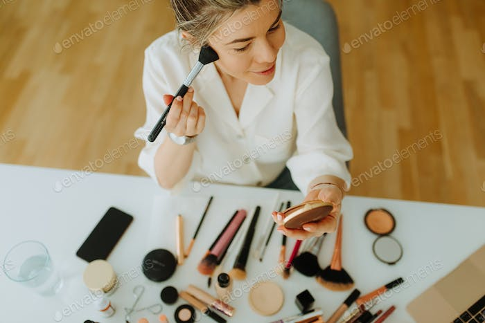 Top view on young woman putting some makeup while sitting in front of table with makeup set.
