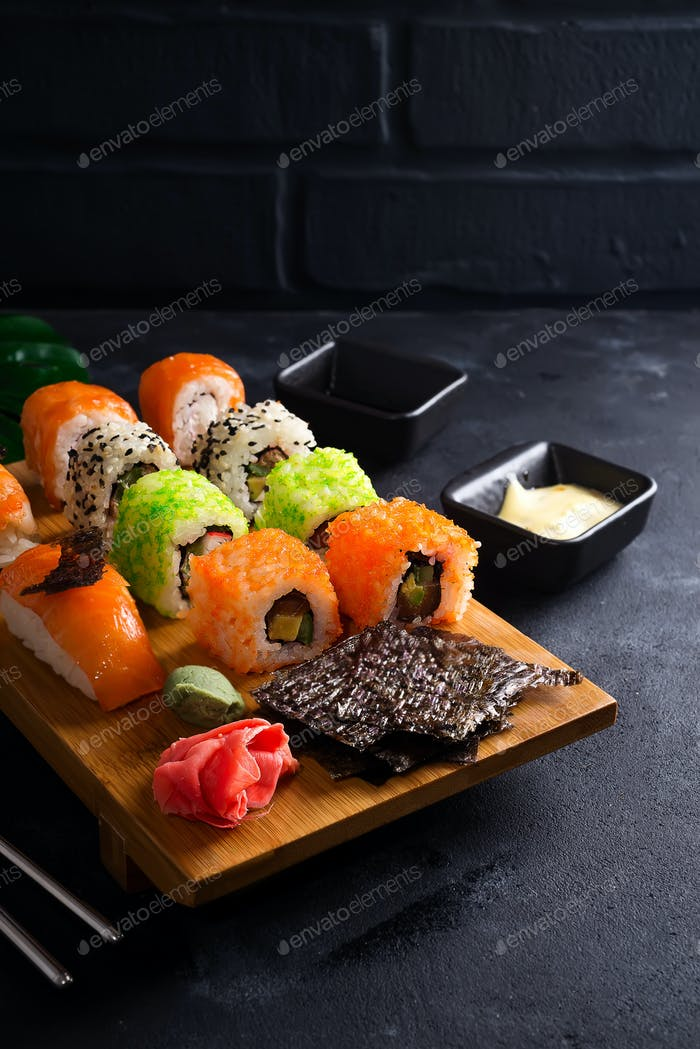 Asian food background with black iron teapot and sushi set on wooden plate on black stone table
