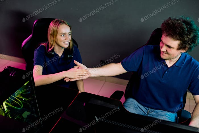 Young cheerful female and her friend shaking hands while sitting by desk