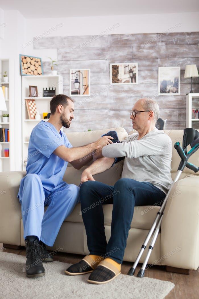 Молодой ассистент в доме престарелых, проверяющий артериальное давление