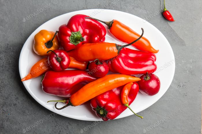 Chili and bell pepper on white plate, slate background, top view
