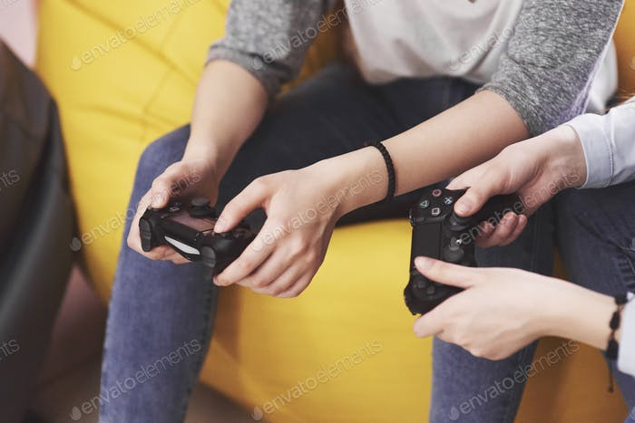 Zwillingsschwester spielen auf der Konsole. Mädchen halten Joysticks in den Händen und haben Spaß