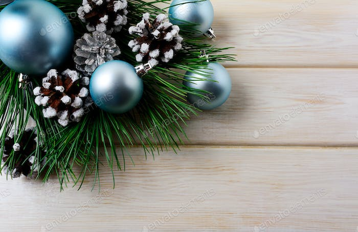 Christmas background with blue ornaments and snowy pinecone
