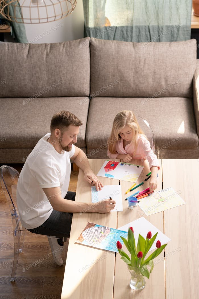 Young man teaching his little daughter how to draw with color pencils