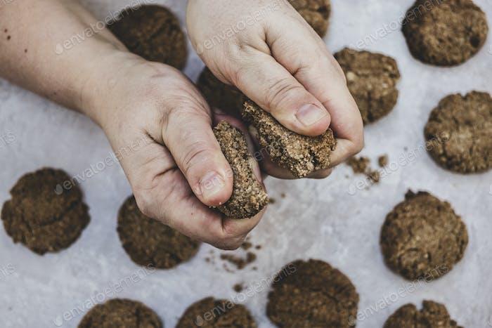 Hoher Winkel Nahaufnahme der Person bricht frisch gebackenen Schokoladenkeks in zwei Hälften.