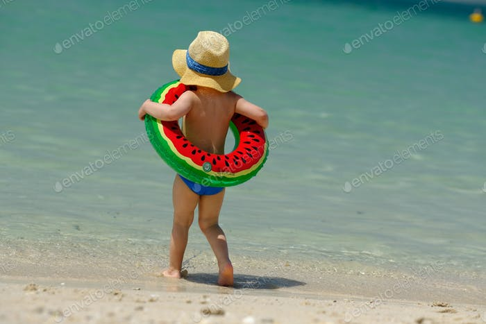 Toddler boy with swim ring on beach