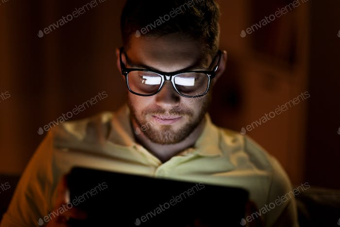 young man with tablet pc networking at night