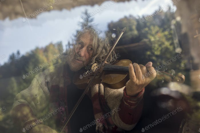 Senior man playing violin behind glass window