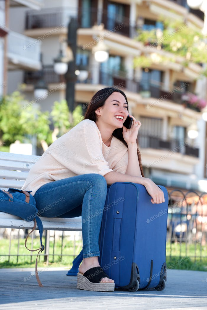 Beautiful woman talking on phone outside with luggage