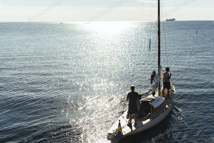 Three people sailing on lake