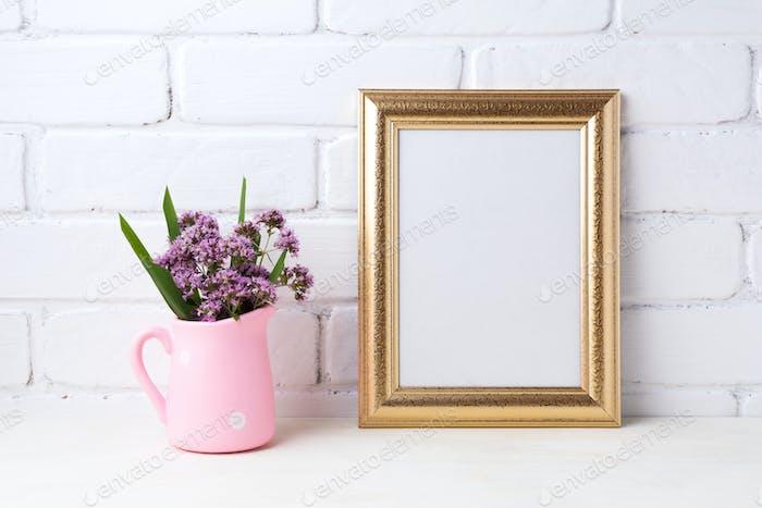 Golden  frame mockup with purple flowers in pink rustic pitcher