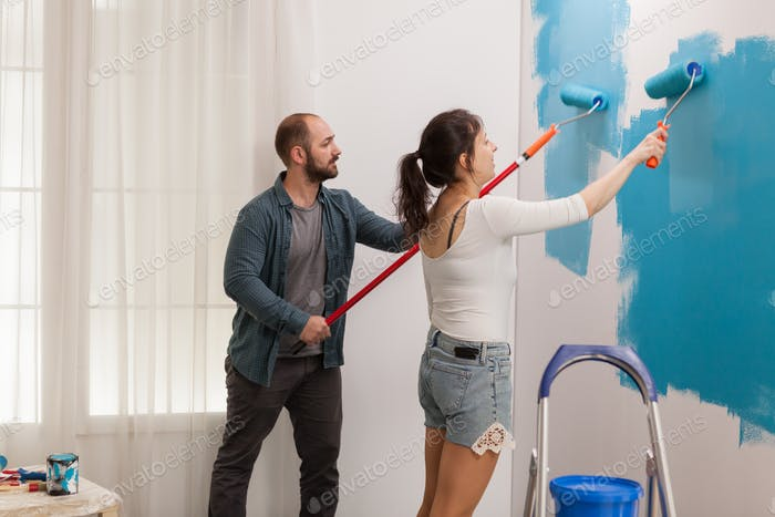 Young couple painting the wall