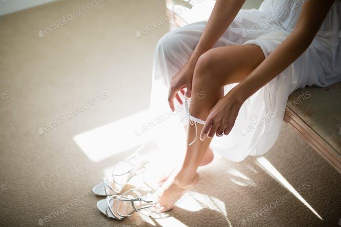 Bride wearing stockings in living room