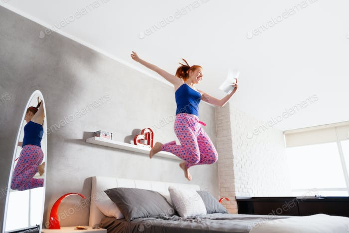 Good News For Happy Young Woman Girl Jumping On Bed