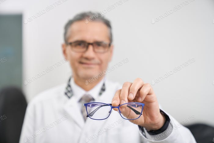 Selective focus of glasses in hands of oculist in clinic