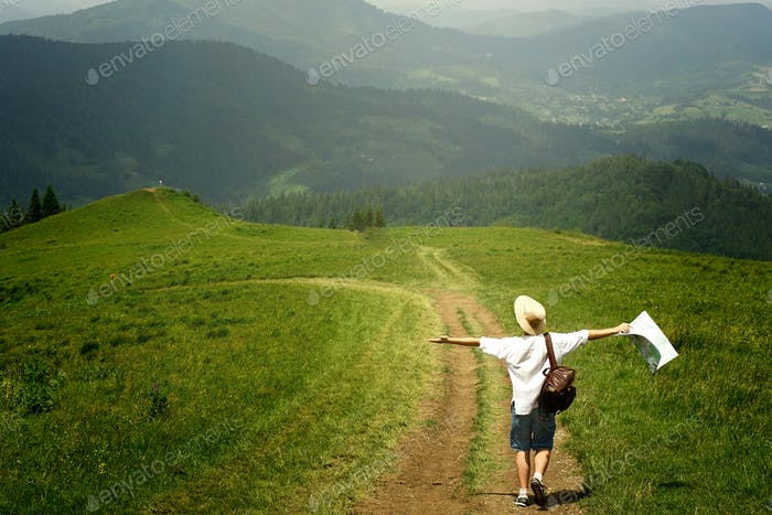 Traveler holding map and walking to top of sunny hill on background of amazing mountains