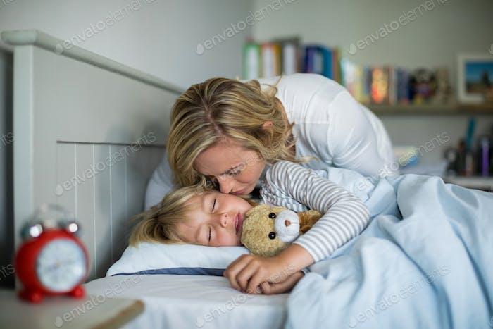 madre besos su hija en el dormitorio