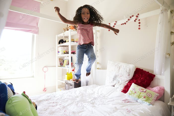 Young Girl Having Fun Jumping On Bed In Bedroom