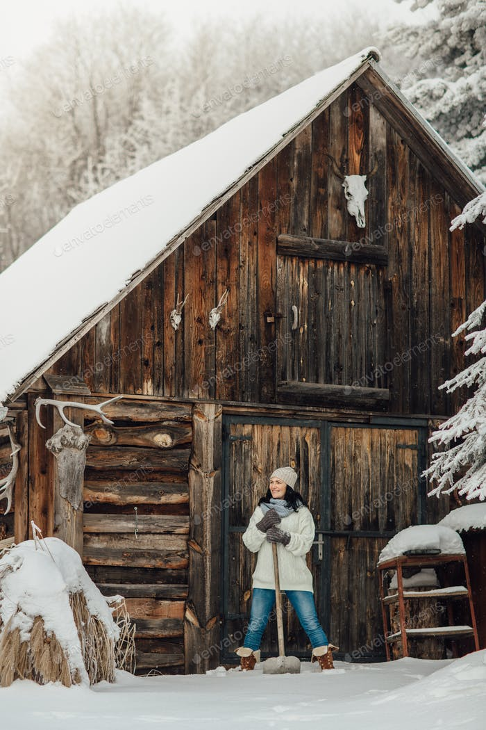 Frau schaufelt Schnee im Winter