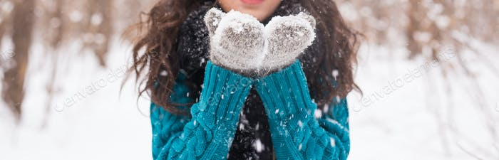 Christmas, holidays and season concept - Close up of young happy brunette woman blowing snow in the