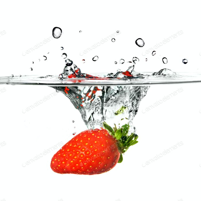 Fresh strawberry dropped into water with splash isolated on whit