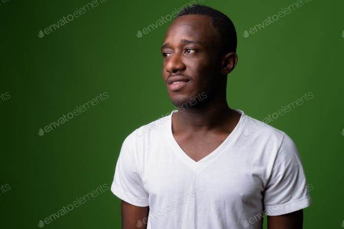 Studio shot of young African man against green background