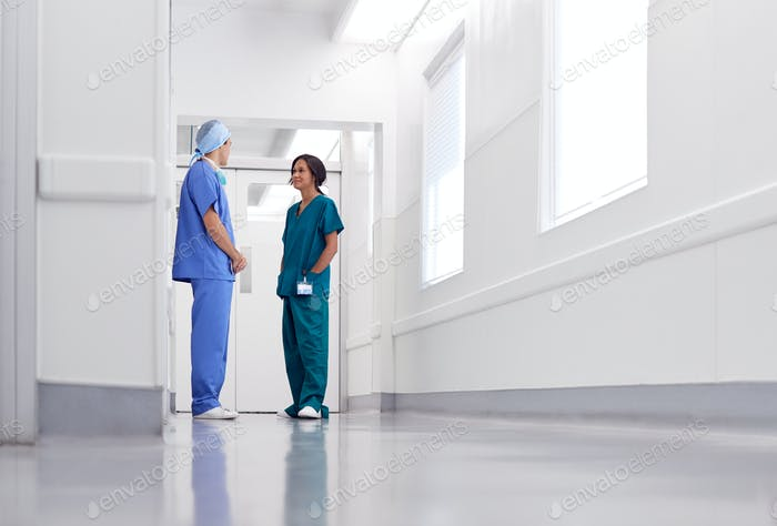 Male And Female Doctors Wearing Scrubs Meeting In Busy Hospital Corridor