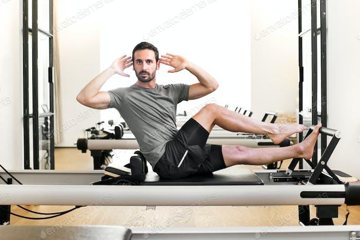 Man performing a pilates single leg stretch
