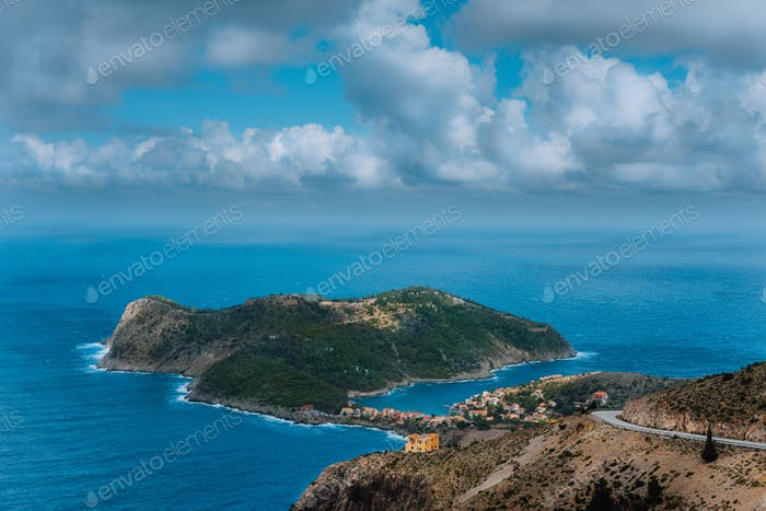 Picturesque view of Assos village and blue sea bay. Stunning cloudscape above the penincula